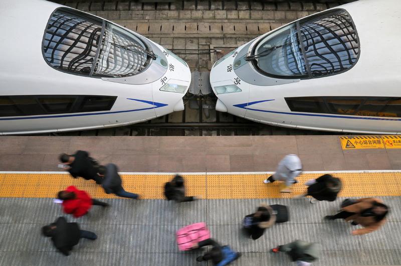 12月27日,旅客在山东烟台火车站下车出站。